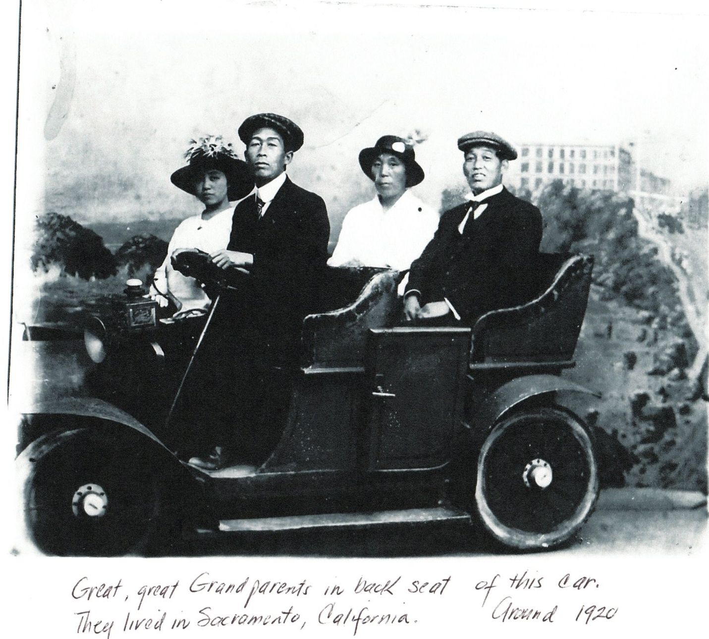 Two couples in a staged photograph in a mockup of an old car, taken in the early 1900s.