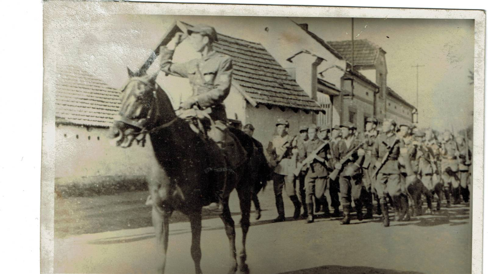 WWII Soldiers being led by soldier on horseback