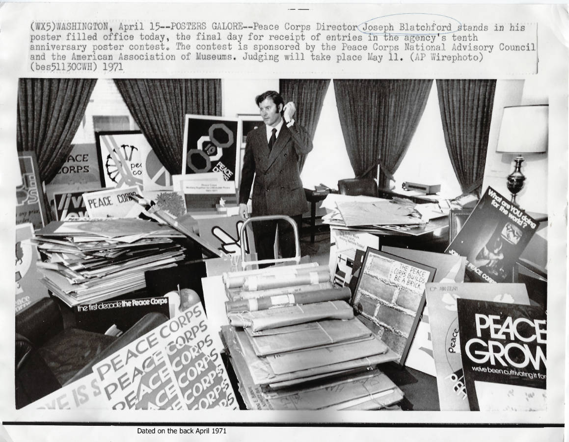 Photo of Joseph Blatchford surrounded by the entries for the Peace Corp Poster contest in April 1971