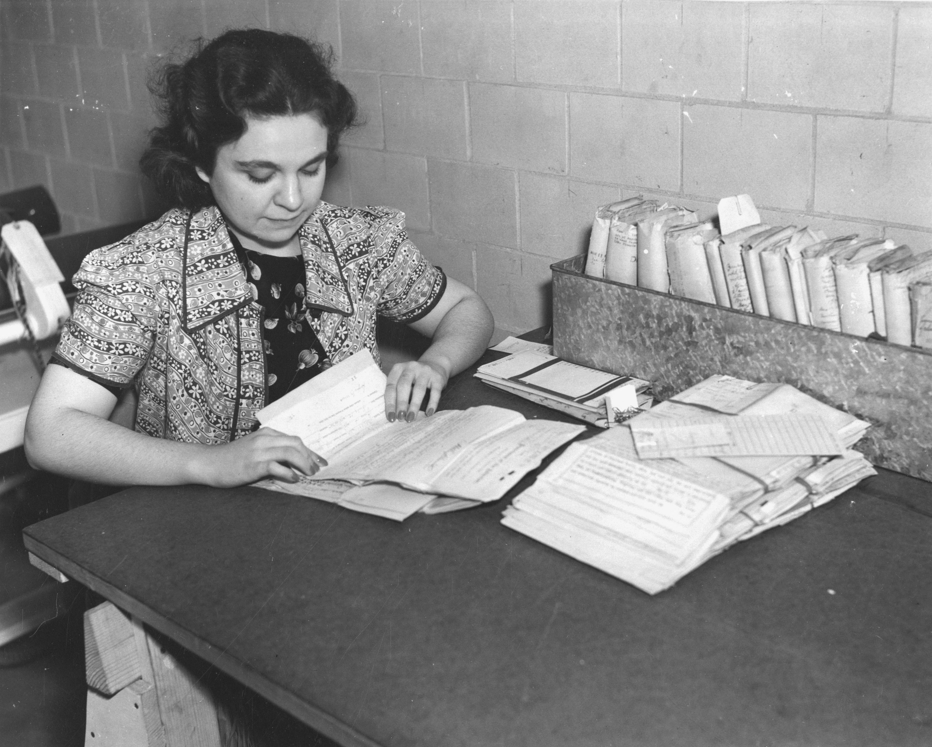 64-PR-26-2 - Worker Unfolding Pension Records, ca. 1939.jpg