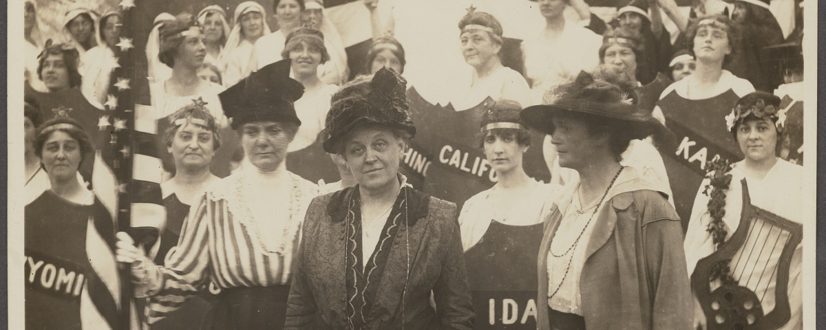 Carrie Chapman Catt and other suffragists gather to fight for their right to vote. Protesters hold banners, shields, and American flags.