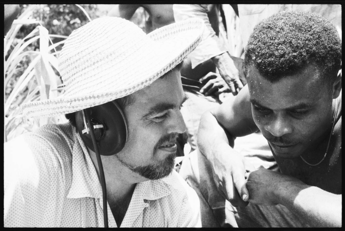Photo of Alan Lomax and Raphael Hurtault listening to playback of an audio recording. La Plaine, Dominica. June 1962
