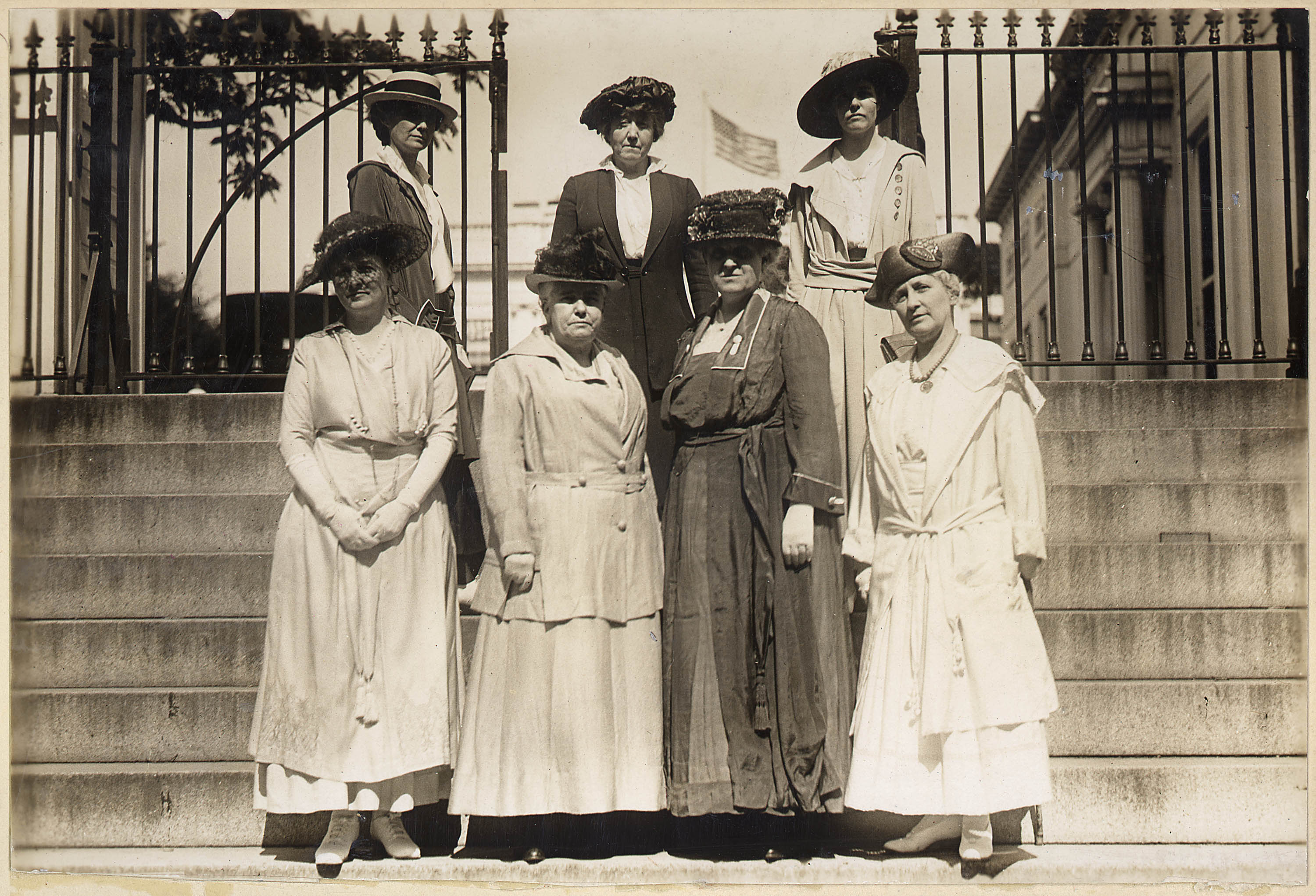 This delegation of officers of the National American Woman Suffrage Association received from President Wilson a memorial to the French women in which he advocates the federal woman suffrage amendment. The picture was made on steps leading to executive offices of the White House. Front row, left to right: Mrs. Wood Park, Dr. Anna Howard Shaw, Mrs. Carrie Chapman Catt, Mrs. Helen H. Gardner: second row, Miss Rose Young, Mrs. George Bass, and Miss Ruth White.